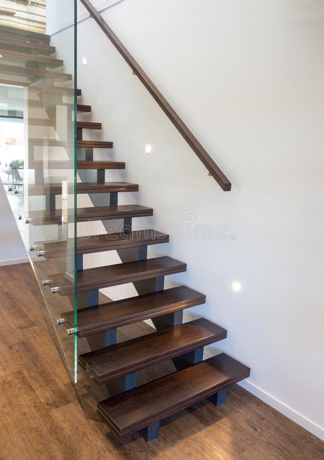Modern wooden staircase with large thick glass balustrade stock image