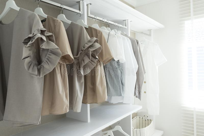 Modern wooden wardrobe with clothes hanging on rail. In walk in closet design interior stock photo