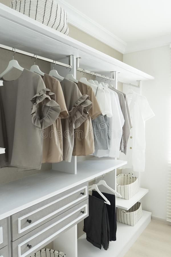 Modern wooden wardrobe with clothes hanging on rail. In walk in closet design interior royalty free stock photography