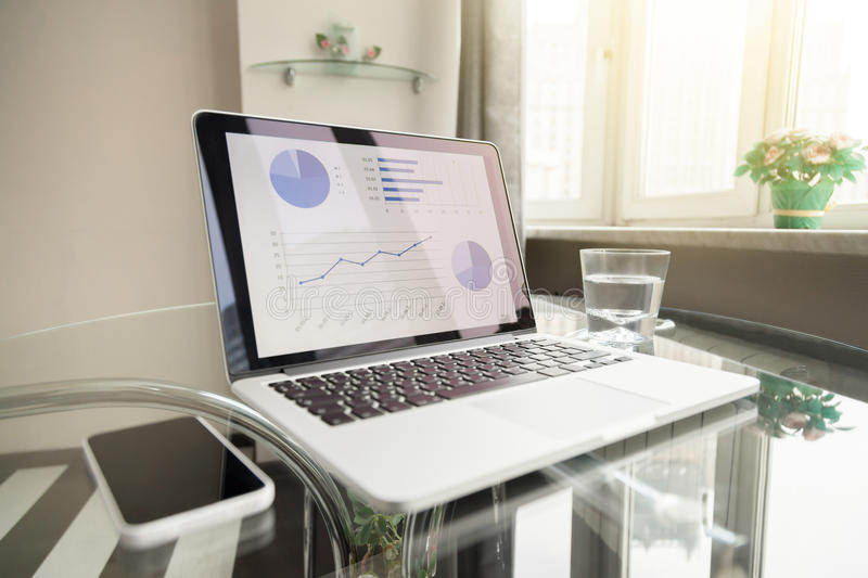 Modern Working place. Modern comfortable organized working place, open laptop with charts on the screen standing on a glass table, smart phone, home based stock photos