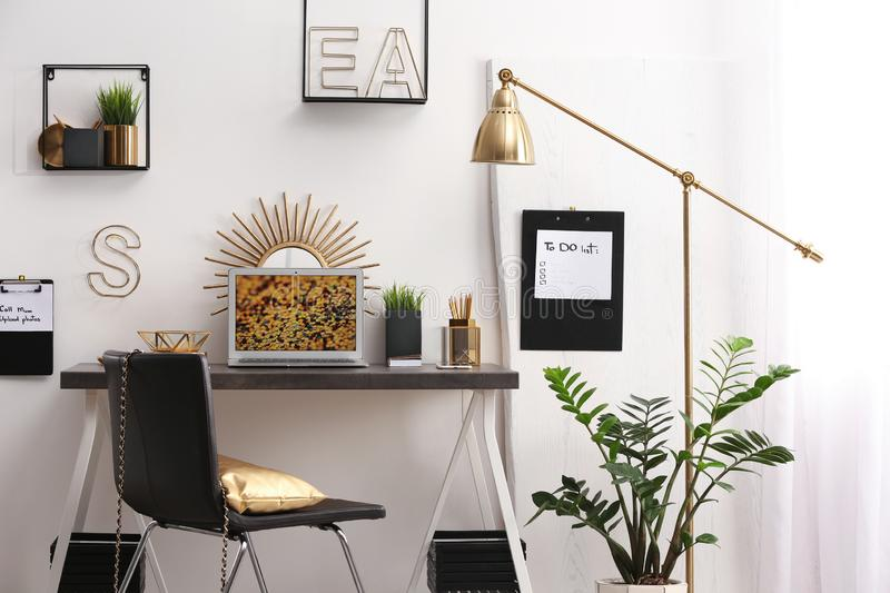 Modern workplace with laptop and golden decor on desk near wall. Stylish interior design royalty free stock images