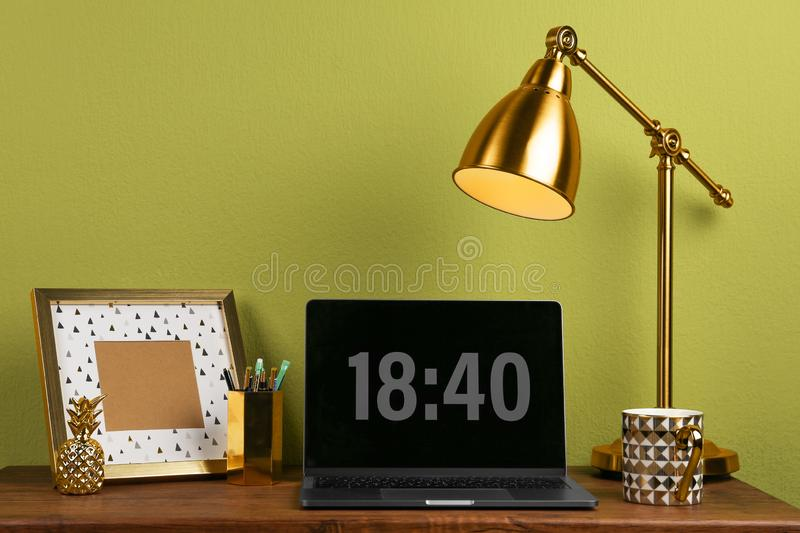 Modern workplace with laptop and golden decor on desk near wall. Stylish interior. Design stock photography