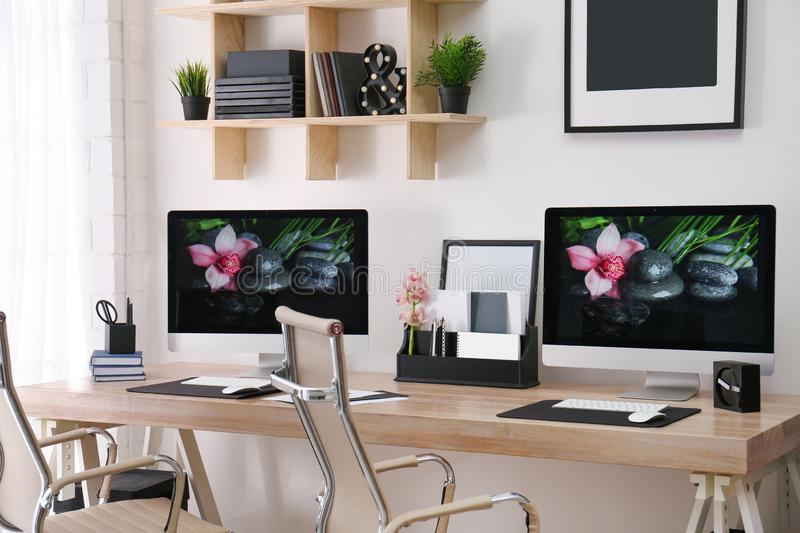 Modern workplace with large desk and computers in room. Stylish interior stock image