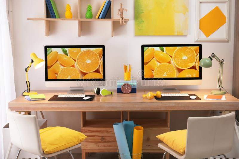 Modern workplace with large desk and computers. Stylish interior. Modern workplace with large desk and computers in room. Stylish interior stock photos