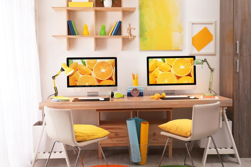Modern workplace with large desk and computers in room. Stylish interior royalty free stock image