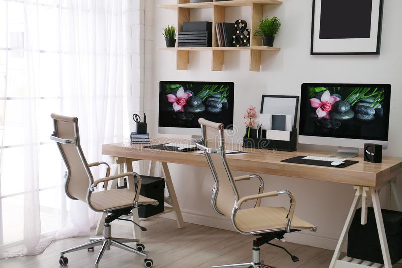 Modern workplace with large desk and computers. Stylish interior. Modern workplace with large desk and computers in room. Stylish interior royalty free stock image