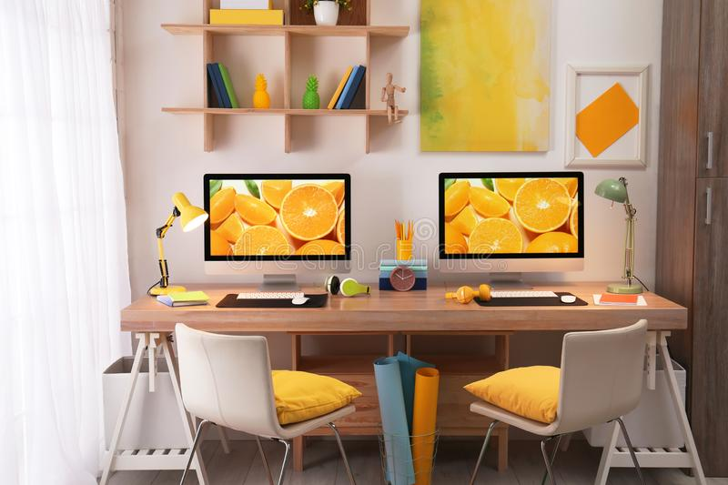 Modern workplace with large desk and computers in room. Stylish interior royalty free stock photo