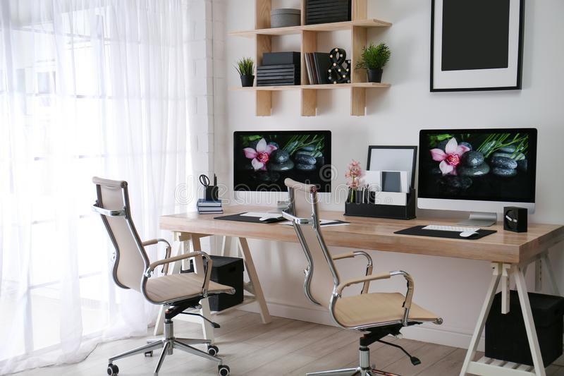Modern workplace with large desk and computers. Stylish interior. Modern workplace with large desk and computers in room. Stylish interior royalty free stock images