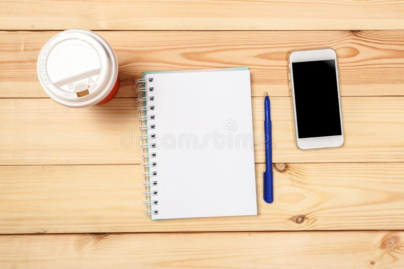 Modern workspace with smartphone,  notebook, pen  on wooden background. Top view. Flat lay style. Modern workspace with smartphone,  notebook, pen  on wooden royalty free stock photography