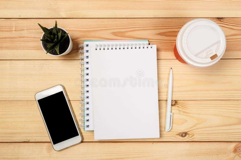 Modern workspace with smartphone,  notebook, pen  on wooden background. Top view. Flat lay style. Modern workspace with smartphone,  notebook, pen  on wooden royalty free stock image