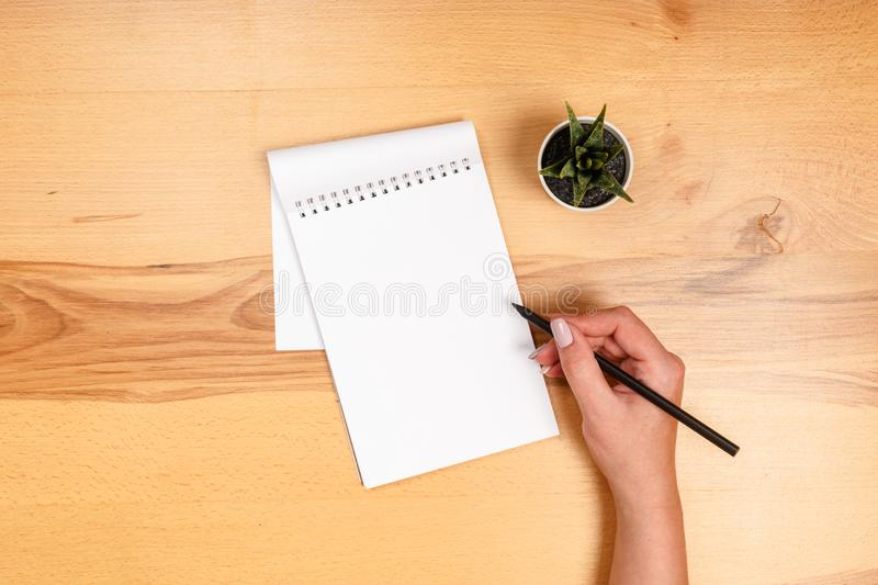 Modern workspace with smartphone, paper, notebook and female hands on wooden background. Top view. Flat lay style. Modern workspace with smartphone, paper stock image