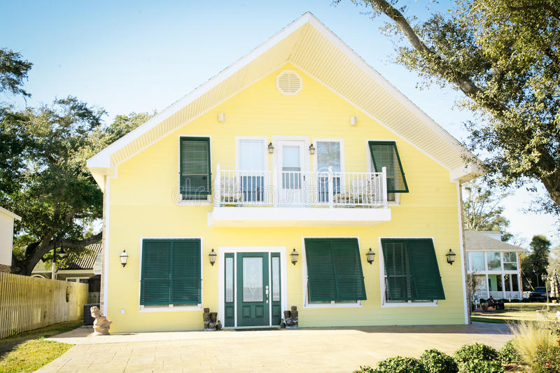Modern Yellow American Home. Modern Southern style American home with white trim, shutters and a balcony stock photo