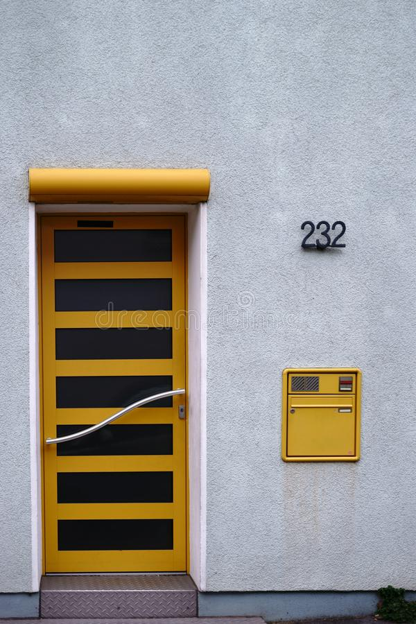 Modern yellow front door with stainless steel handle. The modern front door of a residential building with a curved stainless steel handle and a mailbox stock image
