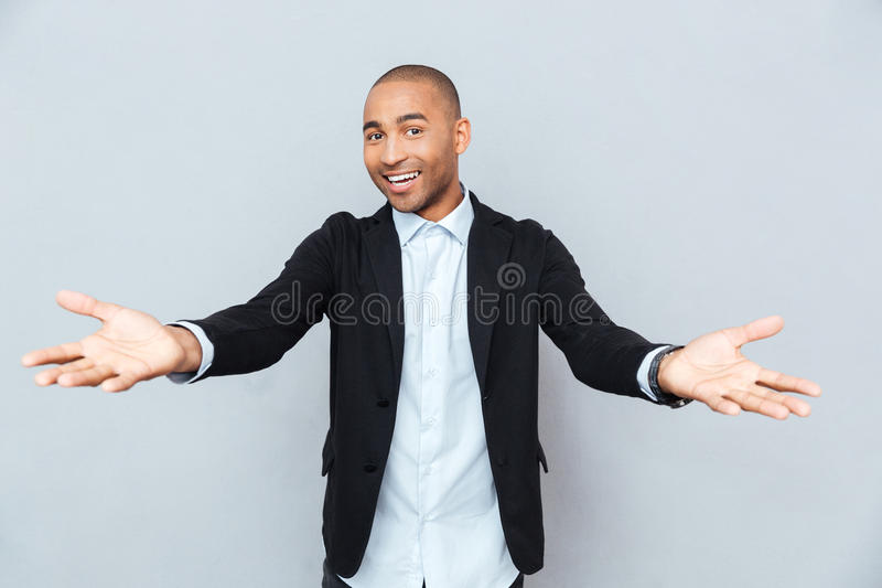 Modern young african man smiling on isolated gray background stock photo