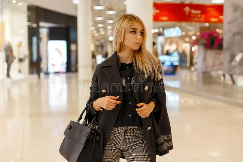 Modern young blond woman in a autumn trendy coat with a vintage warm scarf with a leather black fashion handbag royalty free stock images