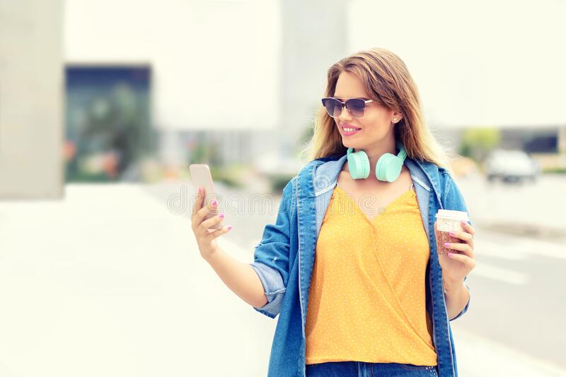Modern young fashion woman influencer having fun at street using cellphone to record a vlog and share content on social media royalty free stock photo