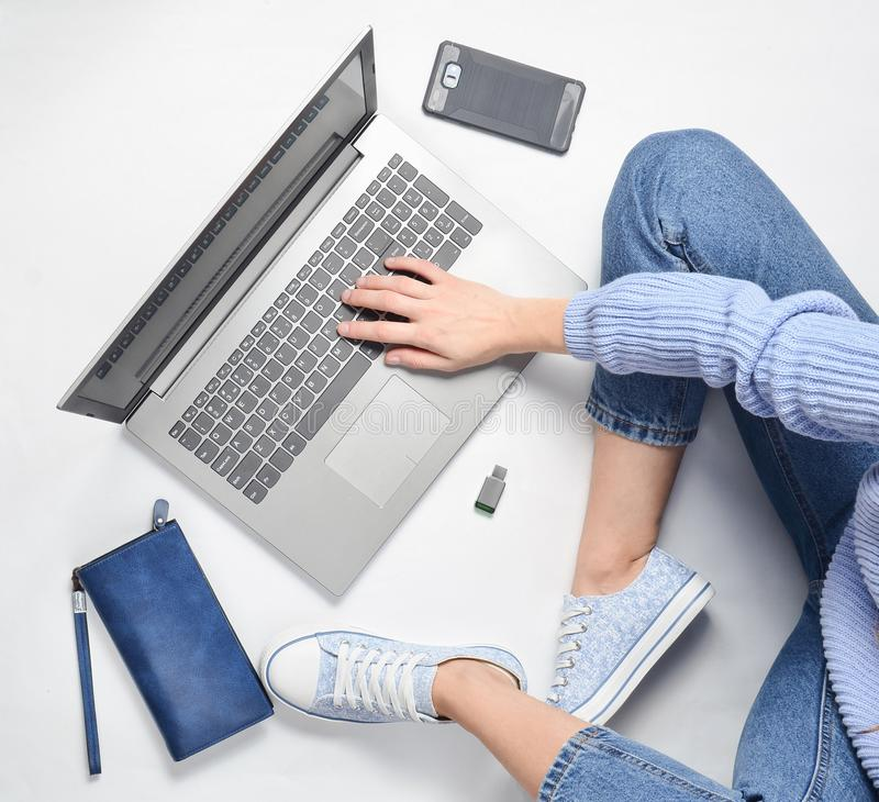 A modern young girl sits on a white floor and use a laptop. Generation z. The concept of freelancing. Working space. Top view royalty free stock photos