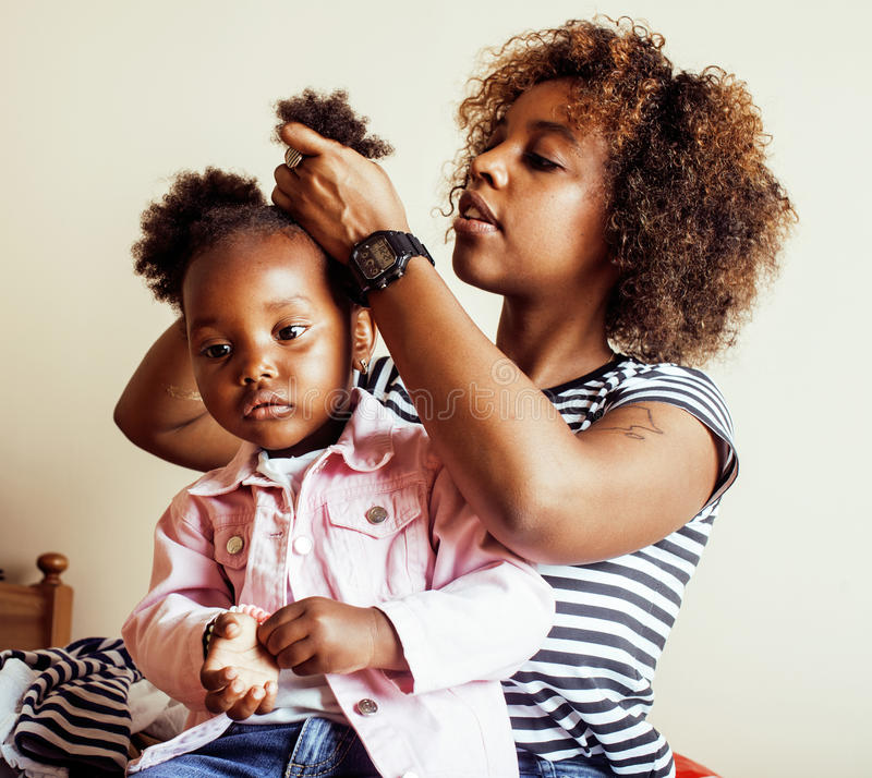 Modern young happy african-american family: mother combing daughters hair at home, lifestyle people concept royalty free stock photography