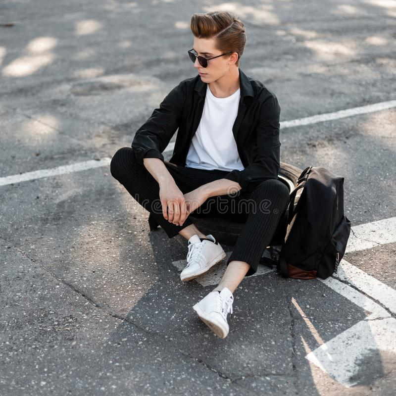 Modern young hipster man in dark sunglasses in fashionable clothes in a white shoes relaxes sitting on the rubber wheel. From the car on a street in the sunny stock photography