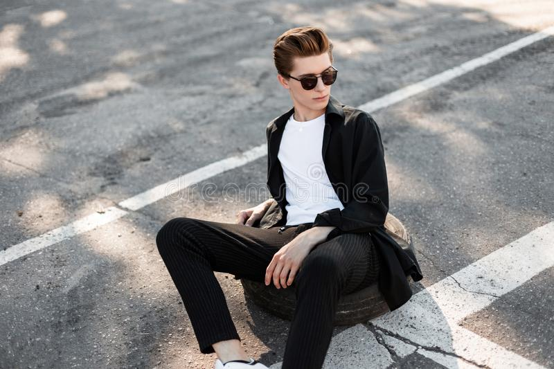 Modern young hipster man in sunglasses in fashionable clothes with a trendy hairstyle relaxes sitting on the rubber wheel. From the car on a street in the sunny stock photo