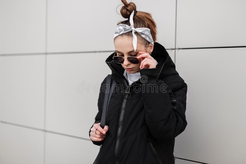 Modern young hipster woman with stylish hairstyle in a bandana in a fashionable black jacket with a stylish backpack. In a knitted golf in stylish sunglasses stock image