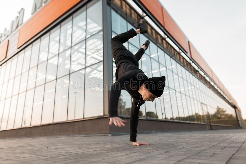 Modern young man dancer in stylish black clothes in a knitted hat dancing break dance on the street near a glass building. Attractive guy doing a handstand in stock photos