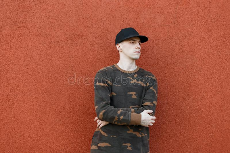 Modern young man in fashionable military clothes in a stylish black American cap poses in the city near the vintage wall. Handsome trendy guy on a walk on a stock photo
