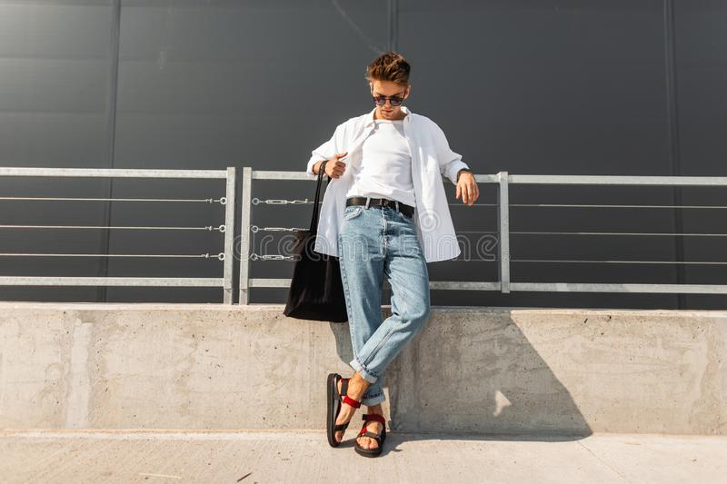 Modern young man hipster in fashionable summer white clothes in sunglasses in stylish red leather sandals with a bag stands. On a sunny day near a gray building royalty free stock photos