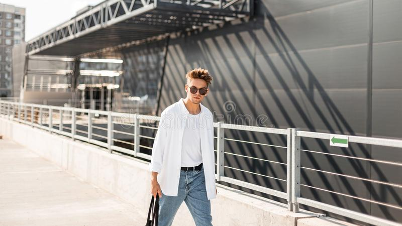 Modern young man hipster with stylish hairstyle in fashionable summer clothes with a black cloth bag in vintage sunglasses walks. Around the city near a gray royalty free stock photography