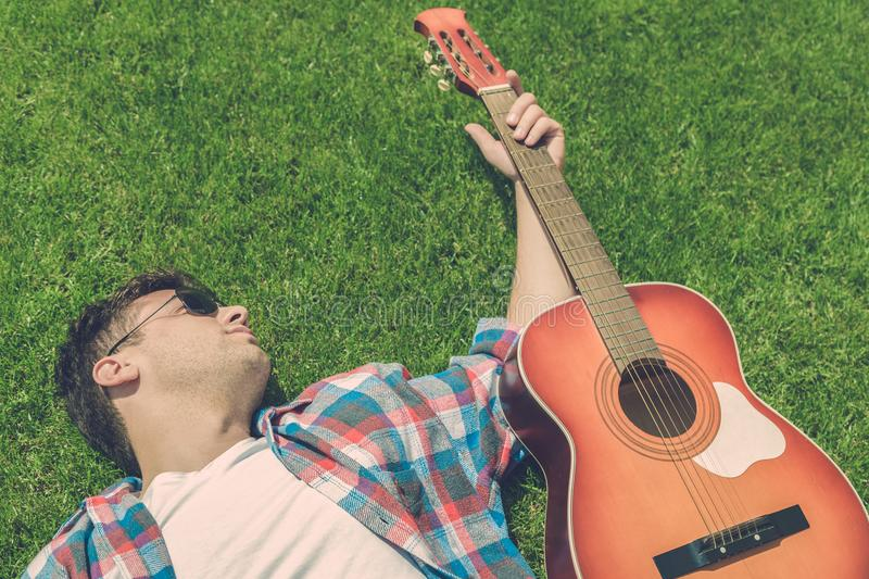 Modern young man lying on grass and holding acoustic guitar stock photos