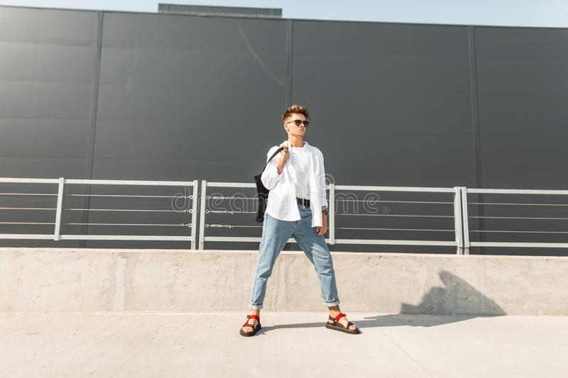 Modern young man model in fashionable clothes in sunglasses in stylish red leather sandals with a bag stands on a summer sunny day. Near a gray building. Urban stock photos