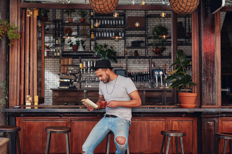 Modern young man reading a book in cafe stock photos