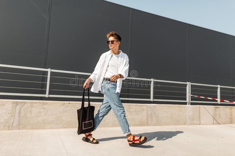 Modern young man in stylish clothes in sunglasses in red leather sandals with a vintage black bag travels on a bright sunny day. Near a gray building. Trendy stock photography