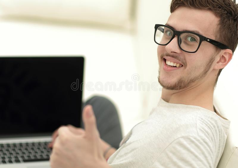 Modern young sitting in front of the open laptop and showing thumb up stock image