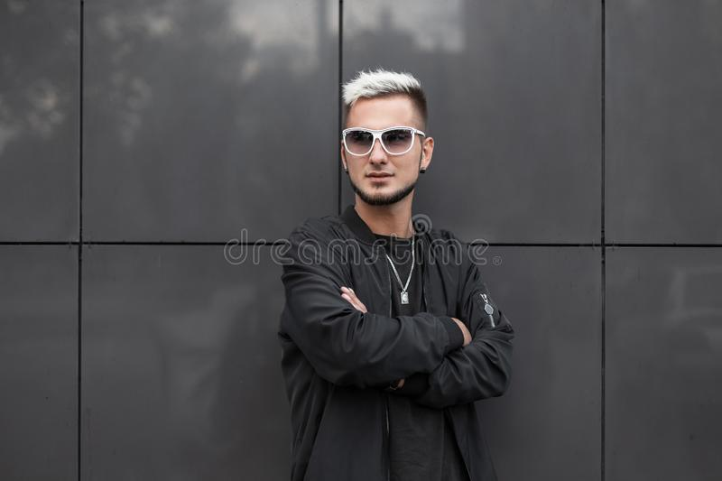 Modern young stylish man model in fashionable black jacket in trendy sunglasses in t-shirt with a hairstyle posing. Near a modern gray wall in the city royalty free stock images
