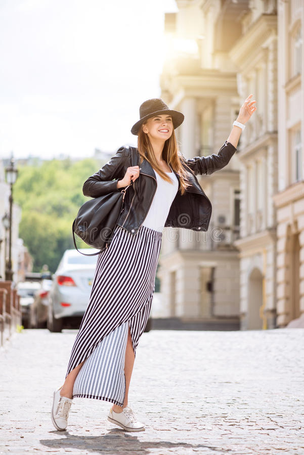 Modern young woman in a big city. Hitchhiking. Cheerful and very happy modern young woman hailing a taxi being in a big city royalty free stock photography