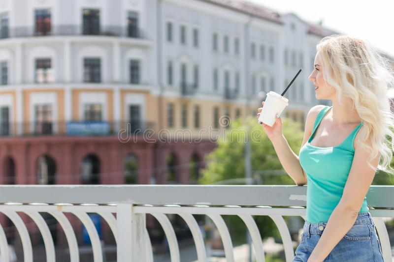 Beautiful Young Woman Drinks Coffee on the Street of the City. Copy Space stock image