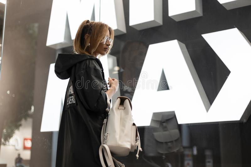 Modern young woman with a hairstyle in a trendy long jacket in vintage glasses with a fashionable leather white backpack walks. Around the store near the glass stock photography