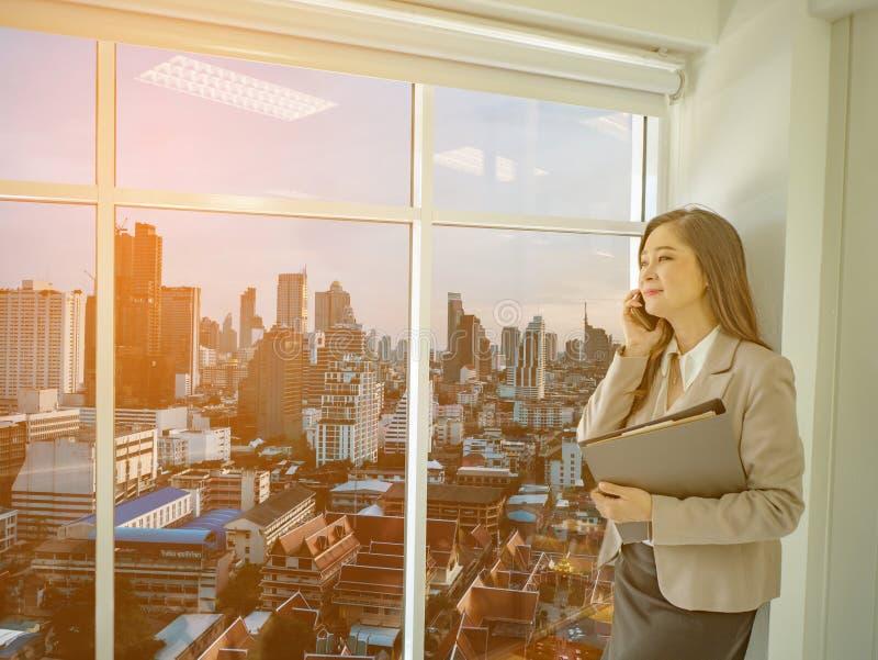 Moderna affärskvinnor använder mobilephonen medan blicken på staden arkivfoton