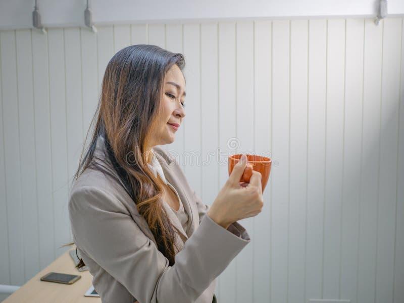 Moderna affärskvinnor rymmer hennes kaffekopp eller rånar arkivfoton