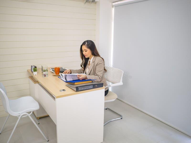 Moderna affärskvinnor tar allvarligt och arbete på hennes skrivbord royaltyfria foton