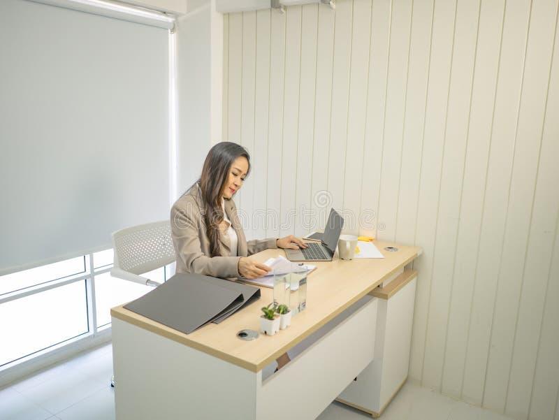 Moderna affärskvinnor tar allvarligt och arbete på hennes skrivbord royaltyfri fotografi