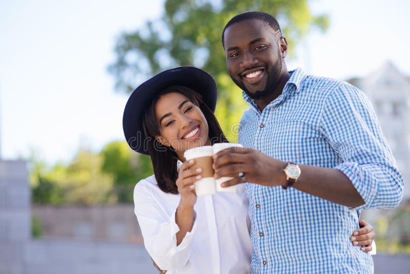 Moderna aktiva par som dricker kaffe arkivfoton