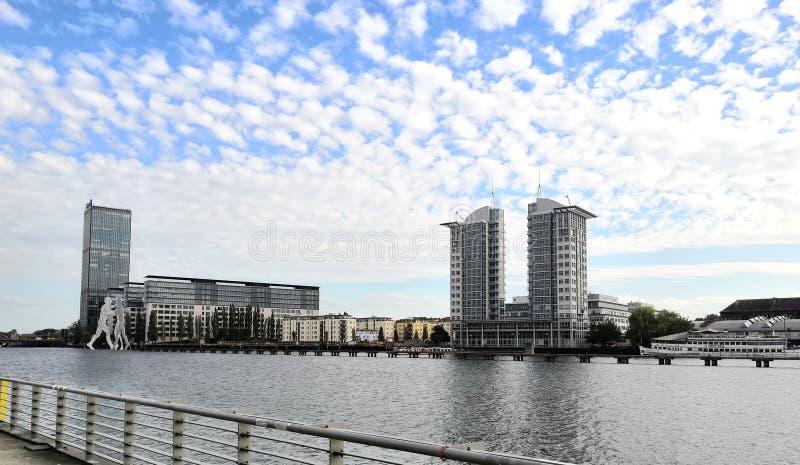 Moderna Berlin: härliga byggnader, molekylmanskulptur och molnig himmel arkivfoton