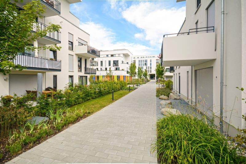 Moderna bostads- byggnader med utomhus- lättheter, fasad av nya låg-energi hus arkivfoton