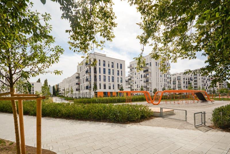 Moderna bostads- byggnader med utomhus- lättheter och barns lekplats, fasad av det nya lägenhethuset arkivfoton
