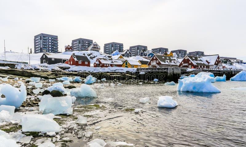 Moderna byggnader och små stugor med isberg som driver i lagun, Nuuk gammal stadshamn, Grönland royaltyfria bilder