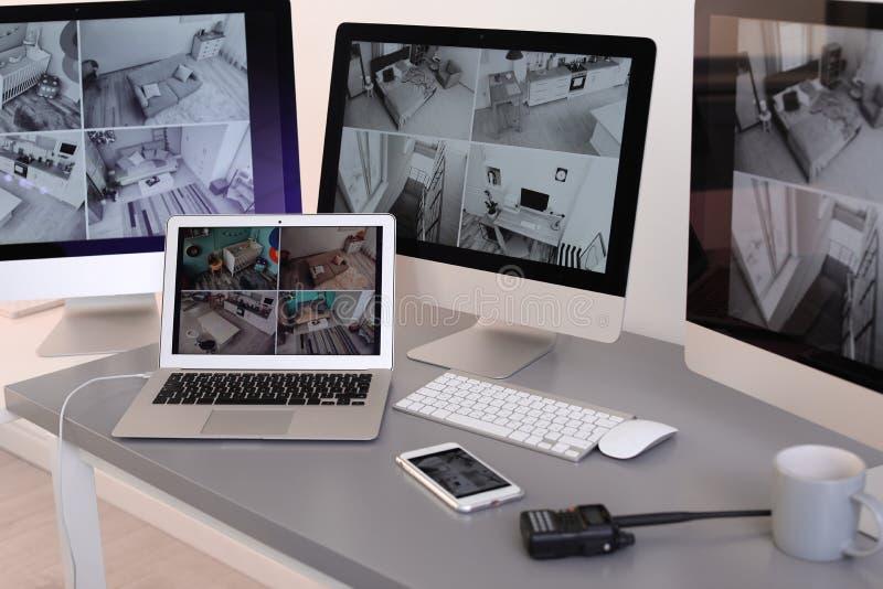 Moderna datorer med video radioutsändning från säkerhetskameror på vakts arbetsplats royaltyfria bilder
