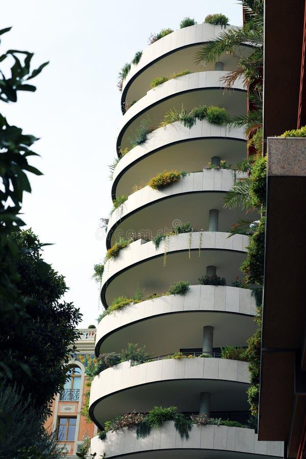 Moderna Ecologic skyskrapor med mycket gröna växter på varje balkong arkivfoto