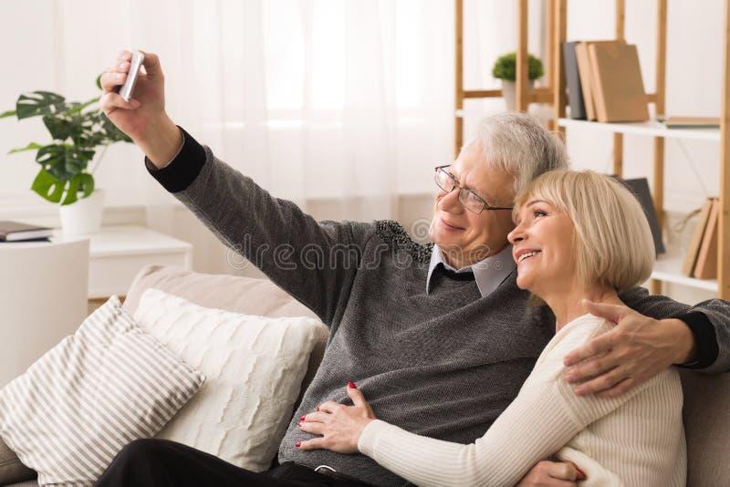 Moderna höga par som gör selfie på smartphonen royaltyfri foto